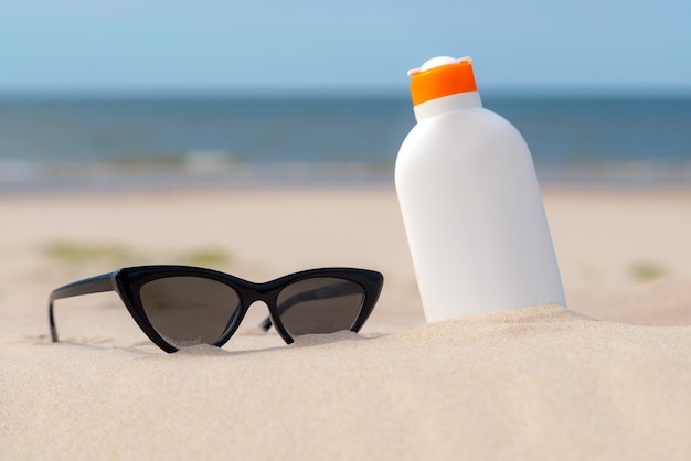Sunscreen protection lotion and sunglasses in the sand on a sunny day at the beach.