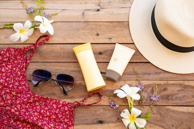 Sunscreen spf50, body lotion, sunglasses, dress and hat of lifestyle woman relax in summer