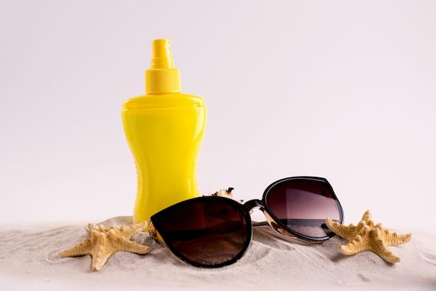 日焼け止めスプレーボトルと夏の麦わら帽子のビーチシューズとサングラスを白いコピースペースに。夏休みバナーのコンセプト。