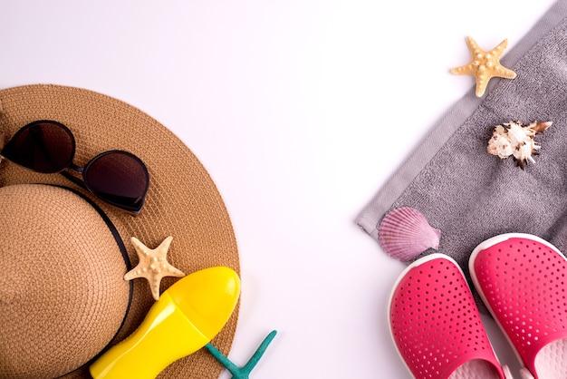 日焼け止めスプレーボトルと夏の麦わら帽子のビーチシューズとサングラスの上面図フラットレイの背景。夏休みバナーのコンセプト。