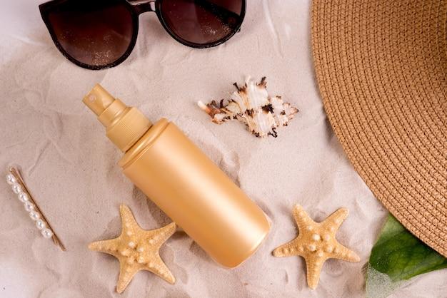 Баллончик с солнцезащитным спреем на песчаном пляже, украшенном различными ракушками