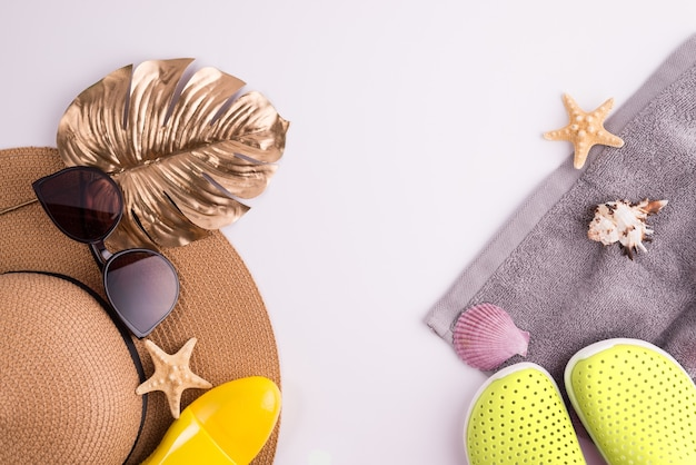 Sunscreen spray bottle and summer straw hat beach shoes and sunglasses top view flat lay background. summer vacation banner concept.
