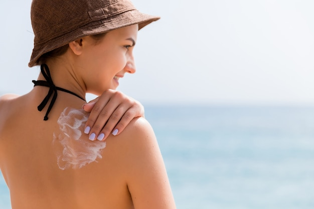 日焼け止め日焼け止め。美しい夏の日に日光の下で屋外の肩に日焼け止めクリームを置く帽子をかぶった女性。