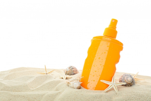 Sunscreen with starfish and seashells on clear sea sand isolated on white background. summer vacation
