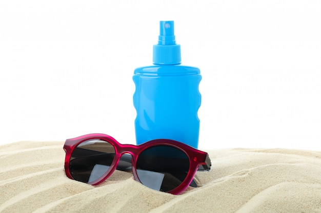 Sunscreen with sunglasses on clear sea sand isolated on white background. summer vacation