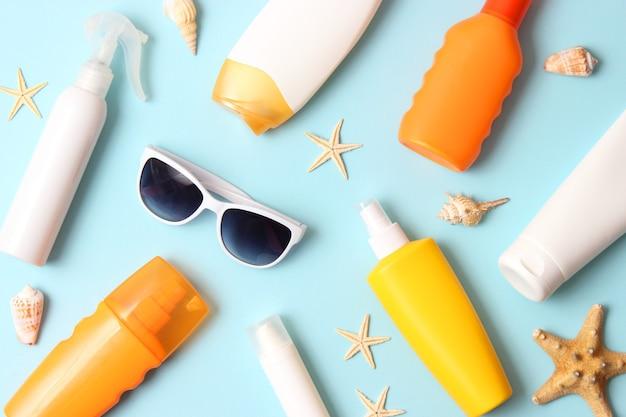 Солнцезащитные кремы на цветном фоне. защита кожи от ультрафиолетовых лучей. фото высокого качества