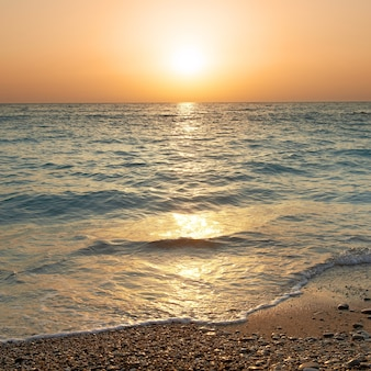 Закат над морем. большое солнце и волны на пляже