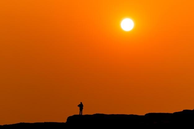 サンパンボークウボンラチャタニタイの山の前景にある夕日とオレンジゴールドのシーンとシルエットの小さな観光客