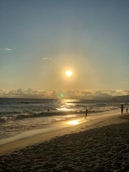Закат на пляже барра-да-тижука в рио-де-жанейро, бразилия. море со спокойными волнами.