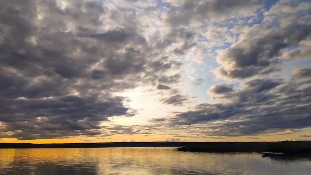 静かな湖の海岸に沈む夕日。水の反射