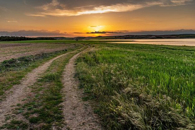 素敵な小道と貯水池のある夕暮れの夕日