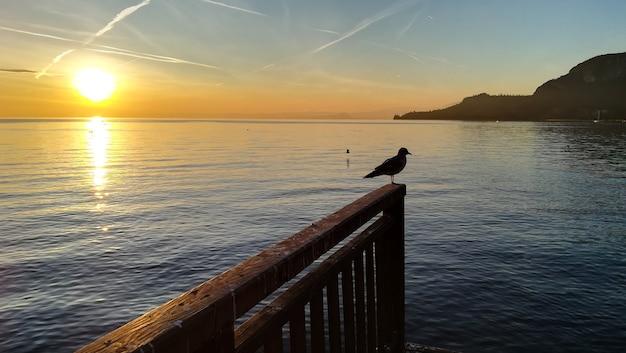 イタリア、ガルダ湖の夕日。イタリアの風景。遠近法の桟橋