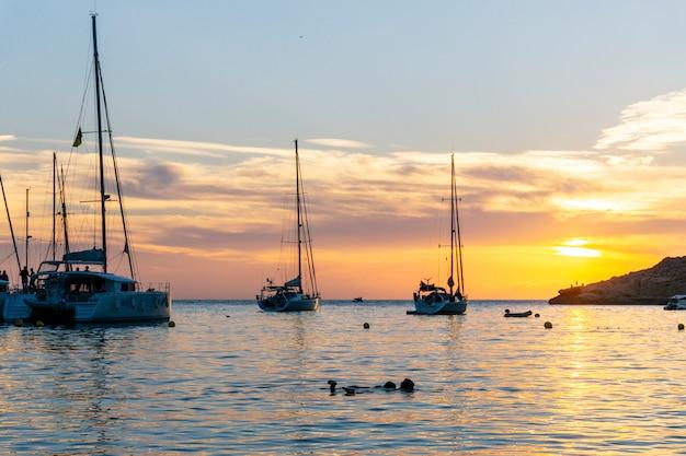 イビサ島の夕日。泳いでいる2人の若い女性と数人の船が停泊し、劇的な色の変化が見られる海に沈む壮大な夕日を眺めている人々