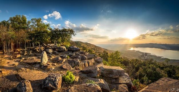 川と石の山の風景に沈む夕日