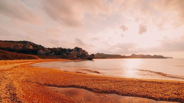 바다에서 일몰입니다. 바다, 바위가 많은 해안선과 모래 해변, 황금빛 하늘과 태양, 야외 여행 배경의 아름다운 전망. 장군의 해변. 크림.