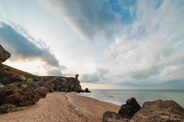 바다에서 일몰입니다. 바다, 바위 해안선 및 모래 해변, 야외 여행 배경의 아름다운 전망. 장군의 해변. 크림.