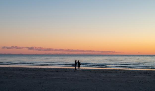 海に沈む夕日、海と同じ高さの太陽、そしてカジュアルな通行人