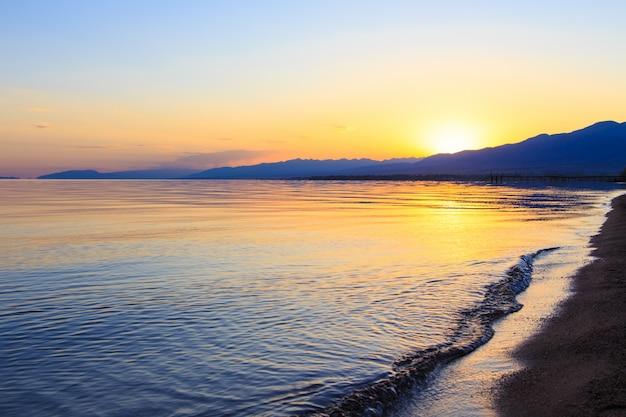 山を背景に海の夕日