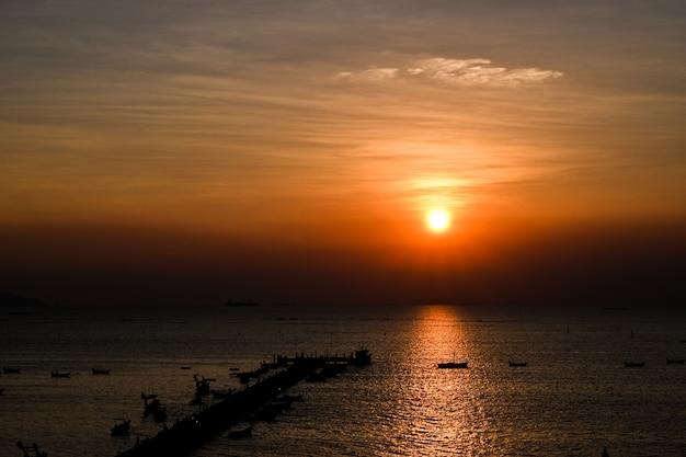 ボートで囲まれた海沿いの橋の夕日。