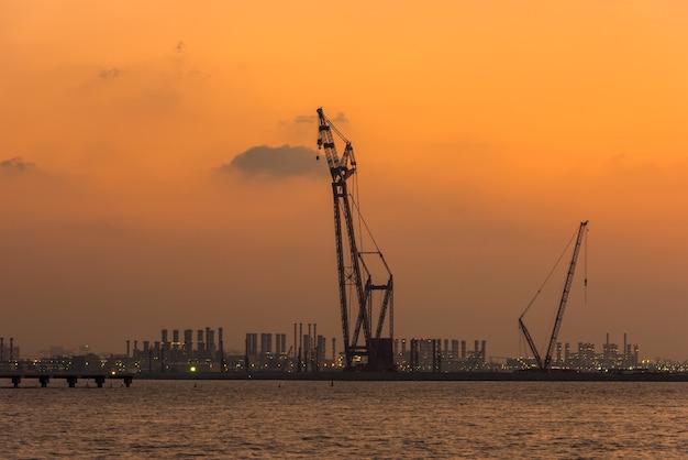 アラブ首長国連邦のドバイ港に沈む夕日。明るい空のクレーンのシルエット