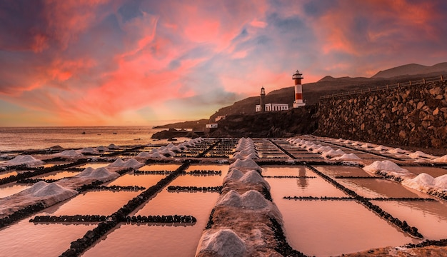 Закат на маяке фуэнкальенте рядом с солончаками, на маршруте вулканов к югу от острова ла-пальма, канарские острова, испания