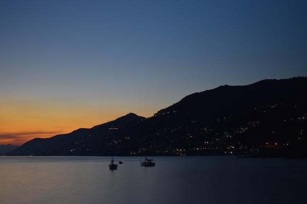 海に沈む夕日、雲と色がすべての色合いに反映されています