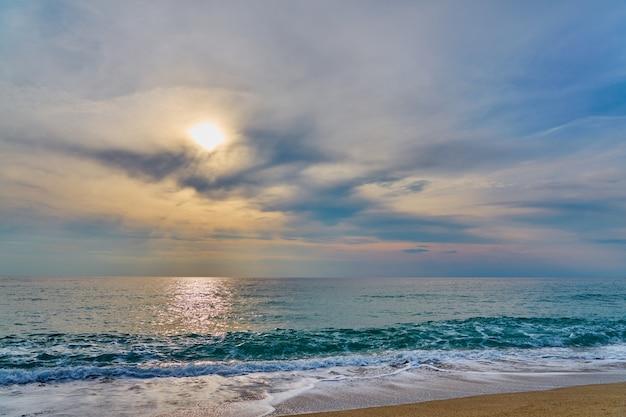 熱帯のビーチに沈む夕日、泡が砂に当たる波。