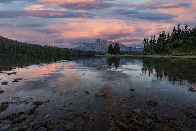 カナダ、バンフ国立公園のトゥージャック湖に沈む夕日。