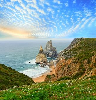 花崗岩の岩と海の崖のある日没の大西洋の海岸。ポルトガル、ウルサビーチのロカ岬(カボダロカ)からの夕景。