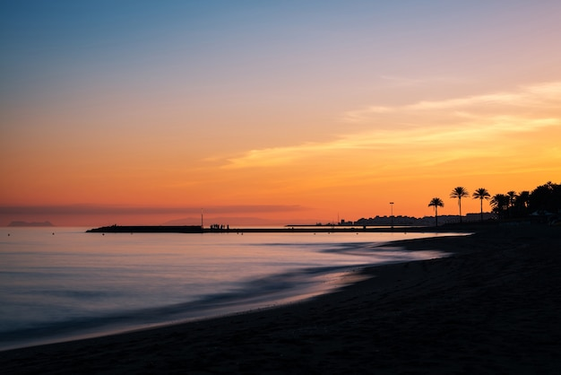 Sunset at a beach in the costa del sol in marbella, with the silhouette of a pier and gibraltar.