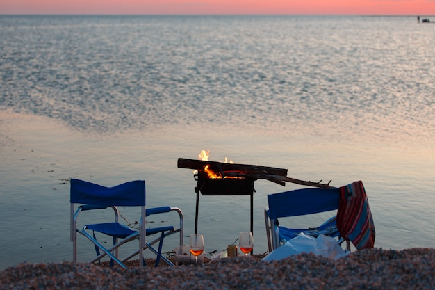 Sunset on the beach with bbq, two camp chairs and a couple of glass of beer or wine.
