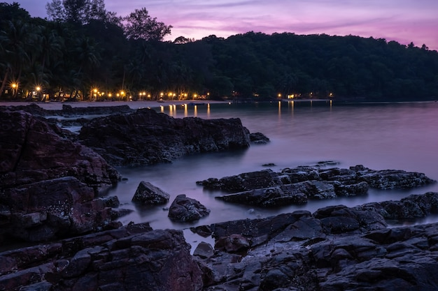 大きな黒い岩に沈む夕日の美しいシーンとビーチリゾートからの光があります