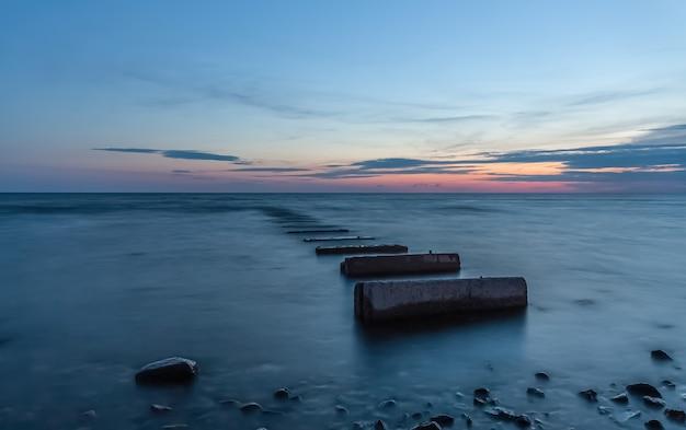 물에 콘크리트 블록으로 바다 일몰