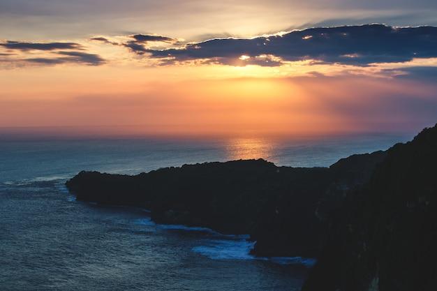 일몰 흐린 하늘입니다. 바다, 절벽 발리 섬입니다. 배경. 인도양과 밝은 일몰 조명 아래 절벽의 놀라운 탁 트인 전망. 야생의 손길이 닿지 않은 자연의 아름다움.