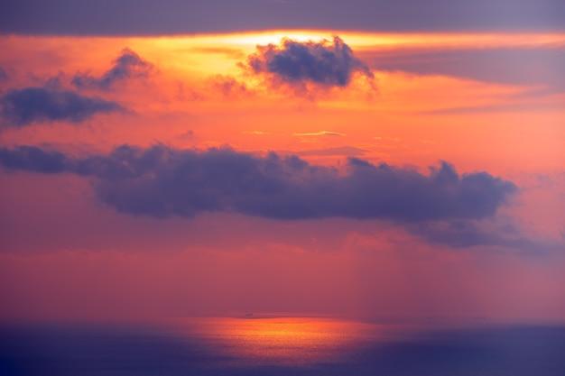 바다 물 위에 일몰 흐린 하늘입니다. 밝은 주홍색, 푸른 색조의 놀라운 풍경. 수면 위에 짙은 구름이 있는 밝은 하늘. 태양 빛 반사입니다. 야생의 손길이 닿지 않은 자연의 아름다움.