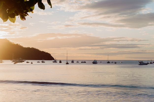 Sunset in coco beach in costa rica, mountain, boats warm colors.