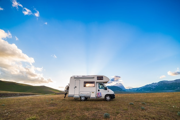 Небо заката драматическое над автофургоном в высокогорье кампо-императоре, абруццо, италия. эпические облака над уникальным ландшафтом нагорья и скалистых гор, альтернативная концепция отпуска vanlife.