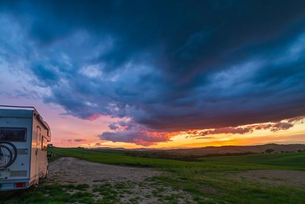 이탈리아 투스카니 오르시아 밸리(orcia valley)의 캠핑카 위로 일몰이 극적인 하늘입니다. 독특한 언덕 풍경 위의 장엄한 구름, 대안적인 밴라이프 휴가 개념.