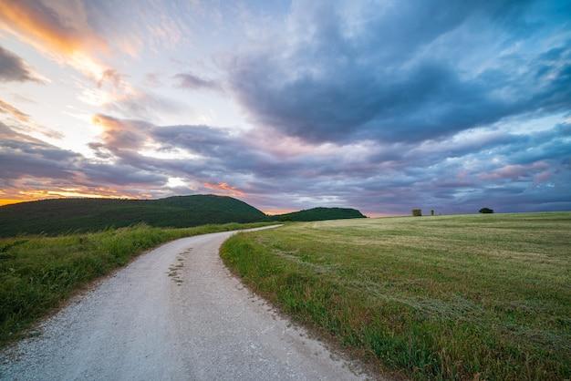 イタリア、マルケ州の田舎道に沈む夕日の劇的な空