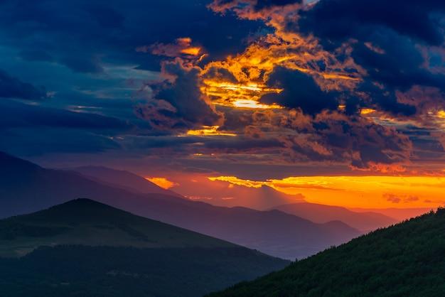 イタリア、マルケ州の山の風景に沈む夕日の劇的な空