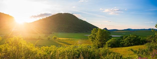 谷と高地の風景に沈む夕日の劇的な空