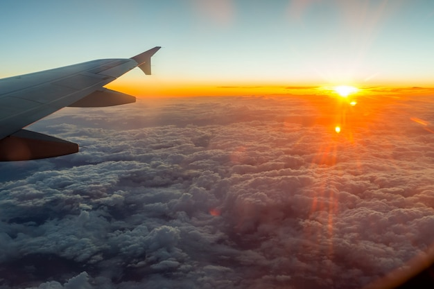 Sunset from the window above the clouds with airplane wing