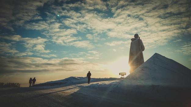 Sunset giant alyosha monument, murmansk. landmark in evening clouds sky.