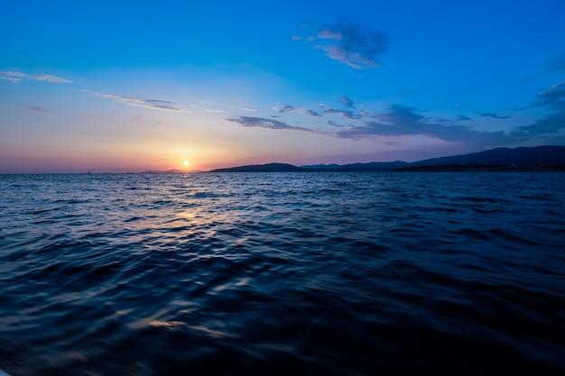 日没。金の海の夕日。ピクチャ海の夕日。金の海の夕日