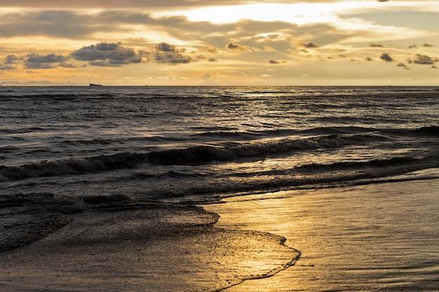 파도와 태양 반사가 있는 바다 해변의 일몰 황금 시간