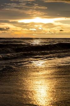 반사된 햇빛과 함께 바다 해변에서 일몰 골든 아워 순간