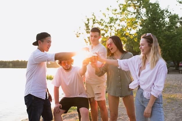Закат группа друзей, чокающихся пивом во время пикника на пляже в солнечном свете