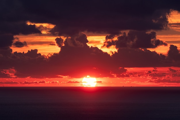 Sunset over horizon in tropical sea with cloudy in evening