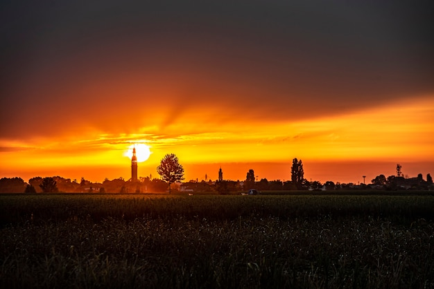 鐘楼、木々、田園地帯のある風景に沈む夕日