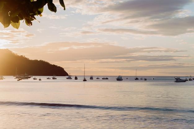 コスタリカのココビーチの夕日、山、ボートの暖かい色。